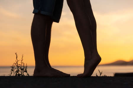 Silhouette of a couple kissing. Legs close-up. Sunset in the background. Valentines day concept.