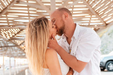Kiss and romance. Handsome Caucasian man kissing a woman. In the background, the ocean and the sky. The concept of a romantic relationship.
