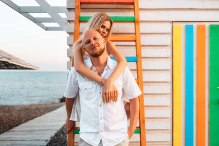 Honeymoon. A young couple of beautiful woman and man posing near colorful ladder. Concept of newlyweds.