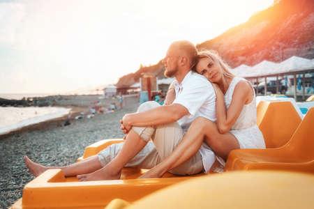 Summer vacation. A young couple of Caucasian man and woman sitting on the catamaran. Honeymoon. 版權商用圖片