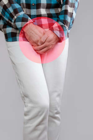 Concept of male sexual diseases. The man holds hands for genitals. Testicular cancer. A red circle, like a hotbed of disease.