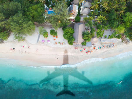 The concept of travel and air travel. Top view of the sandy coast of the ocean, with the shadow on the water from the landing plane. Airplanes shadow at the down side.