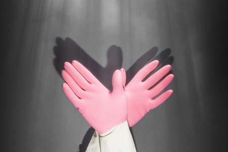 Shadow theater. Hands in rubber gloves shows the figure of a pigeon. On the dark wall, the shadow of the hands in the form of a bird.