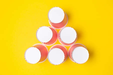 A pyramid of striped red paper cups, on a yellow background. Flat lay. Copy space.