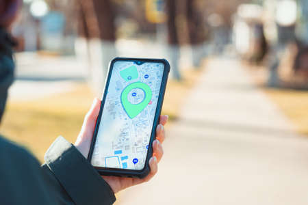 The concept of online navigators and modern technologies. A woman holds a cellphone with the online maps app open and looks at the marked location. Close up of hand. Blurred background. 版權商用圖片