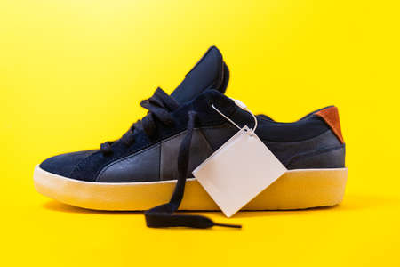 Male's new sneaker made of blue leather on a yellow background. Close up. Mock up. 版權商用圖片