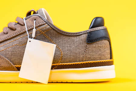 Male's new sneaker made of brown canvas on a yellow background. The back of the shoe, close-up. White label with copy space. Mock up.