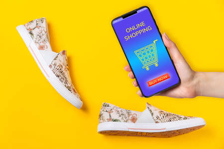 Pair of female's new stylish slip-ons with floral ornament on a yellow background. Female's hand holding a smartphone with page of internet store. Concept of online shopping. 版權商用圖片