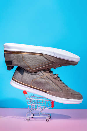 A pair of new stylish man's sneakers lies in a small shopping cart on a pink and blue background. Vertical. Copy space. Close up. Shopping concept.