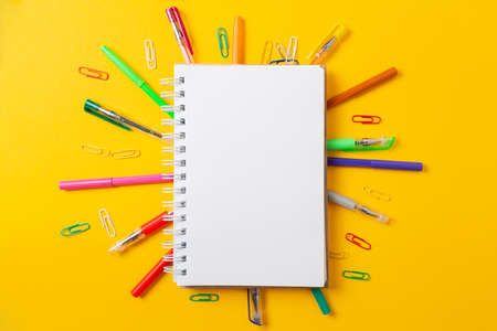 Back to school. Composition with notepad and multicolored pencils, yellow desktop table background. Flat lay, mock up. Copy space. Concept of education.