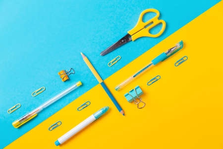 Blue and yellow office supplies on background. Flat lay. Back to school. Education and bussines concept.