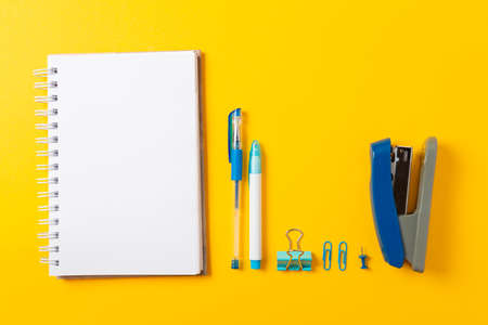 Back to school. Notebook, pencils, clips and stapler on yellow background. Flat lay. Copy space, mock up. Education and bussines concept.