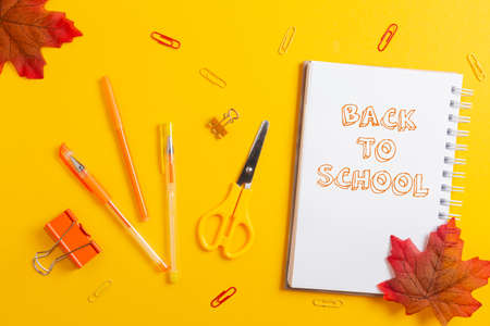 Back to school. Notepad, scissors, clips and pencils on yellow desktop background with maple leaves. Flat lay. Concept of education.