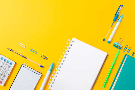 Book, copybook, notepad, clips and pencils on yellow background. Flat lay. Back to school banner with copy space. Mock up. Education and bussines concept. 版權商用圖片