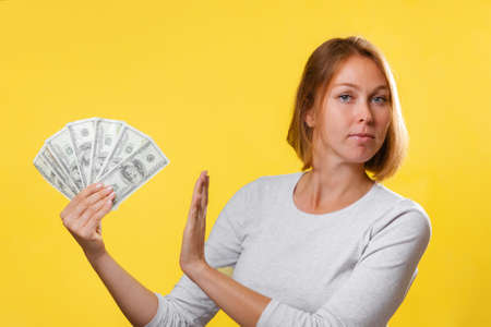 Portrait of a caucasian woman holding a fan of dollars in her hand, and refusing them. Yellow background. The concept of bribery. Standard-Bild