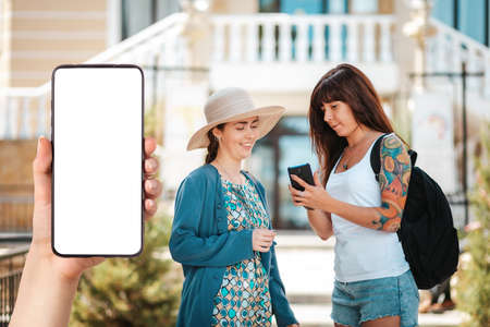Two women chat and watch something on their smartphone. In the foreground and hand holding a smartphone, mock up. Communication and business concept. Standard-Bild