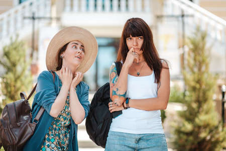 Two young women chat on the street. One woman listens boringly to the story of an emotional interlocutor. The concept of friendship, communication and psychology. Standard-Bild
