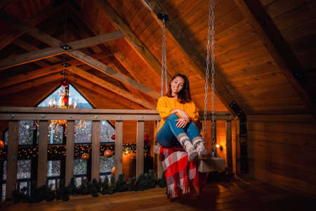 A young smiling woman poses on a swing with her legs neatly folded. In the background is a wooden ceiling and Christmas decoration of the hall.