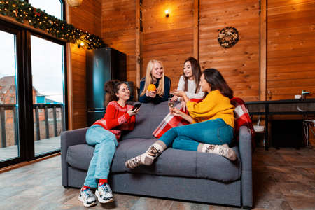 Christmas and new year. Young women sit on the couch and chat with each other. In the background, the interior is rustic, decorated for the winter holidays.
