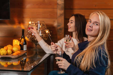 Christmas and new year holidays. Two young happy women sit at a table with champagne glasses and sparklers in their hands.
