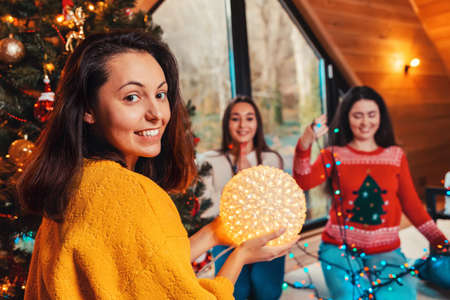 Christmas and new year. Portrait of a young smiling woman holding a lighting ball. In the background, two other women are untangling the lights.