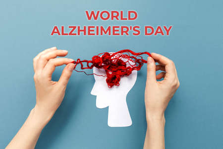 World Alzheimer's day. Female's hands unravel the tangled red threads on the silhouette of the head, representing the brain. Blue background. Flat lay. The concept of mental health.
