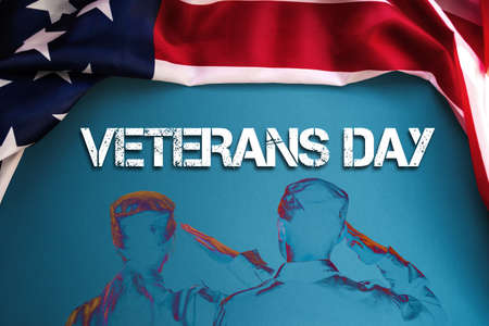 Silhouettes of a two soldiers saluting on a blue background, framed by an American flag. Back view. The concept of the Veterans Day.