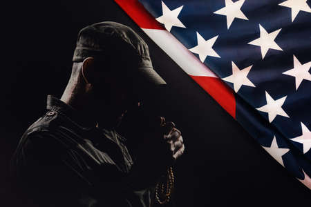 National American holidays. The silhouette of a male praying soldier on a black background with an American flag. Copy space. The concept of Veterans Day.
