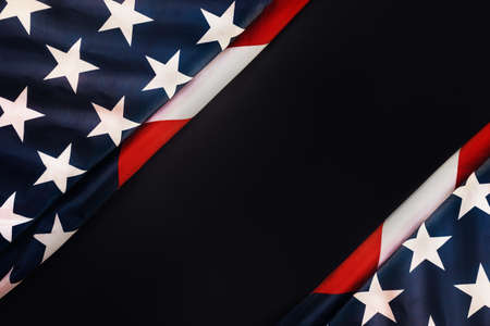 National holidays of the USA. Black background with an American flag. Flat lay. Copy space. The concept of the Veterans Day and Independence Day. Standard-Bild