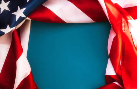 National holidays of the USA. Blue background framed with an American flag. Flat lay. Copy space. The concept of the Veterans Day and Independence Day.