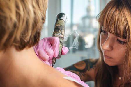 Tattoo-artist in rubber gloves makes a tattoo to a client. Close up of face and hands. Side view. Concept of world tattoo day. Standard-Bild