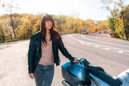 Motorcycle local travel. Young woman in a leather jacket and sunglasses posing near a motorcycle. Empty road on the background. World Motorcyclist Day concept.