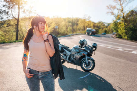 Pretty tattoed girl with a leather jacket poses against the background of a motorcycle by the road. Motorcycle local travel concept.