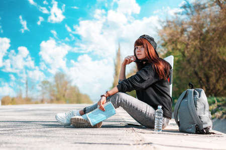A hipster young woman in cap with tattoed hands sitting along the road with a paper map. Copy space. Concept of hitchhiking and local travel.