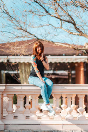 A young woman with tattoed hand sits on the balustrade and smiling. Vertical orientation. Outdoor.