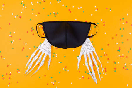 Reusable black virus protection mask and paper skeleton hands. Orange background with decorative stars. Flat lay. The concept of protection from the virus during Halloween.