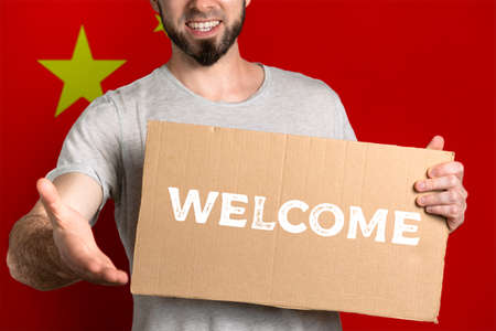 The concept of tolerance for immigrants and people of different life positions. A man holds a cardboard and stretches out his hand to greet. Flag of China. Text welcome.