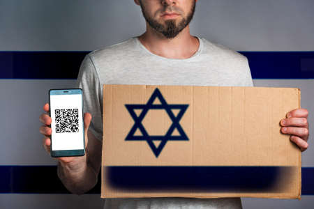 A man with a cardboard and a phone in his hand. The Flag Of Israel. Concept of freedoms and human rights. Copy space.