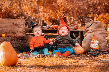 Halloween and autumn holidays. A boy in a dwarf costume and a girl in a witch costume. Outdoor. Preschool child. Standard-Bild