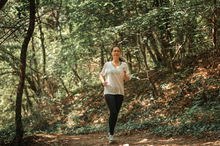 Fitness and sport. Young pretty woman in sports clothes is jogging at forest. The concept of a cardio training and cross-country running. Standard-Bild
