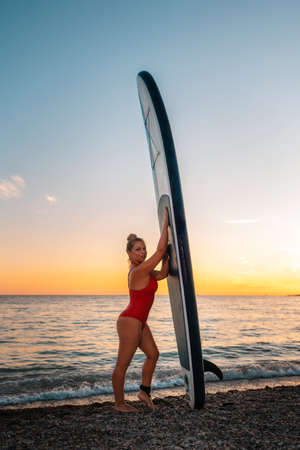 Sexy silhouette of woman in red swimsuit poses with sup board at beach. Vertical. Copy space. The concept of Surfing.