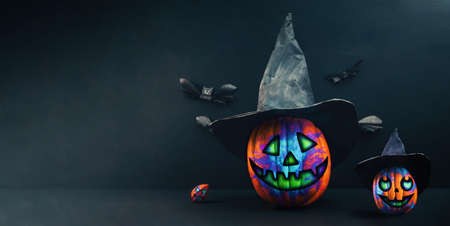 Happy Halloween banner. Two decorated multicolored pumpkin in a black witch's hat with physalis and bats made of paper. Dark background with copy space. Standard-Bild
