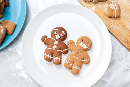 Two gingerbread men, decorated with icing in the form of a medical mask and a screaming face, on a white plate. Top view. The concept of Christmas holidays during the coronavirus. Standard-Bild