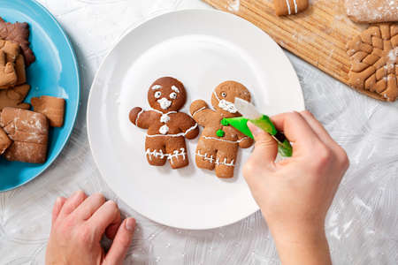 Hand decorates icing cookies. Two gingerbread men with icing in the form of a medical mask and a screaming face, on a white plate. Top view. The concept of Christmas holidays during the coronavirus.