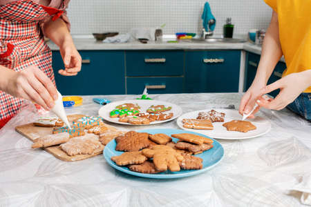 Women decorate gingerbread ising sugar. Close-up of cookies on plates. Indoor. The concept of Christmas cooking.