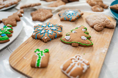 Christmas decorations. Gingerbread decorated with powdered sugar on a wooden Board. The view from the top. Holiday food. Standard-Bild