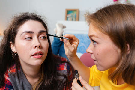 Two young women make up decorative cosmetics. One woman paints another woman's eyelashes with mascara. The concept of LGBT relationships and makeup.