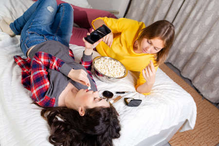 Two young women are lying on the bed, eating popcorn, using smarfton, and decorative cosmetics are lying next to them. Concept of LGBT relationships and recreation at home.