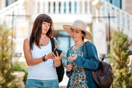 Two women are discussing something emotionally, looking at their smartphone. The concept of communication and modern technology. Standard-Bild