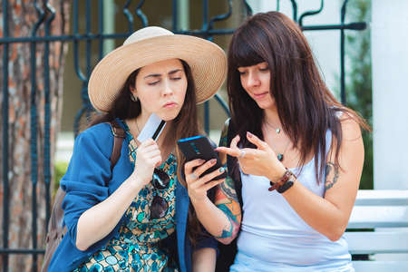 Two women sit on the street, and thoughtfully look at their smartphone, making purchases in an online store. One woman holds a Bank card in her hand. The concept of communication and modern technology. Standard-Bild